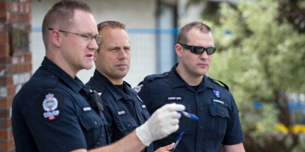 Investigators inspect the scene where a police officer was shot and killed on Monday, in Edmonton, June...