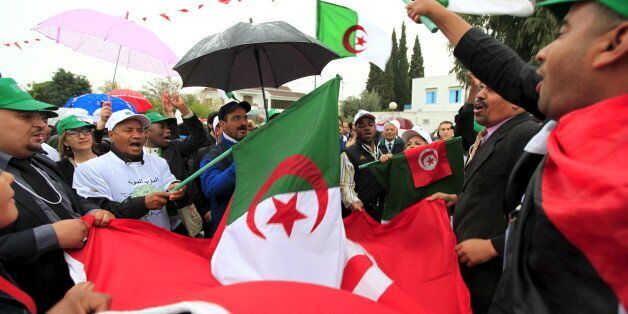 People holding Algerian flags and Tunisian flags march down a boulevard near the Bardo museum, during...