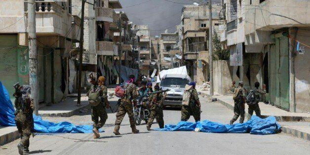 Des membres de forces démocratiques syriennes dans une rue de Minbej en Syrie, le 7 août