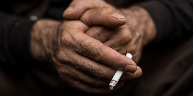 A Kurdish worker smokes a cigarette as he takes a break at a demolition site in Chiba east of Tokyo,...