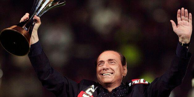 The AC Milan President Silvio Berlusconi lifts the FIFA Club World Cup 2007 trophy before their Italian...