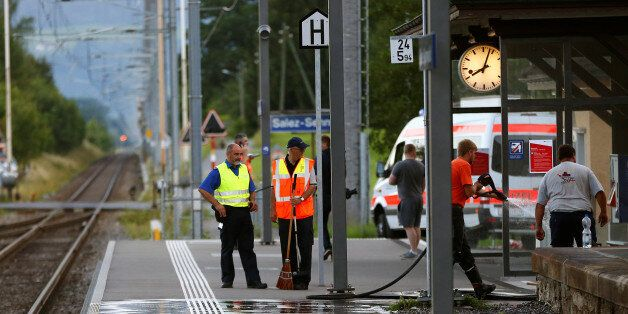A Swiss police officer stands near workers cleaning a platform after a 27-year-old Swiss man's attack...