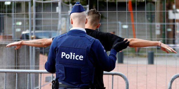A Belgian police officer searches a visitor outside the main police station where a machete-wielding...