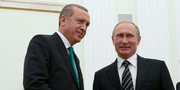 Russian President Vladimir Putin shakes hands with Turkey's President Recep Tayyip Erdogan, left, in...