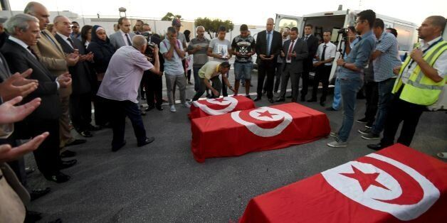Tahar Mejri (back C) reacts as he stands in front of the flag-draped coffins of his four-year-old son...