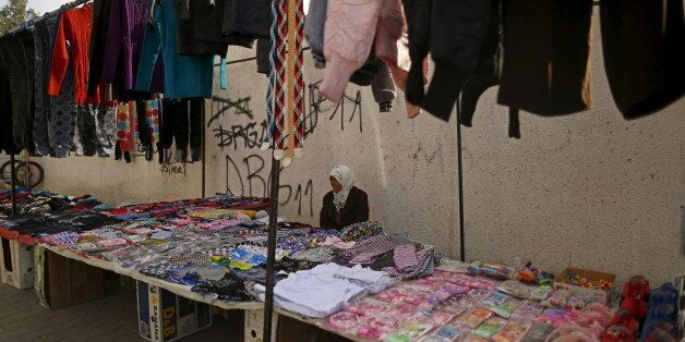 Meriem, 60, a street vendor, sits as she waits for customers in Kasserine, where young people have been...