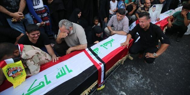 Iraqis mourn next to empty coffins at the site of the explosion in Baghdad's Karrada shopping district...