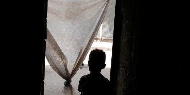 In this Monday, May 16, 2016 photo, A Syrian refugee child leaves a commercial space that a family has...