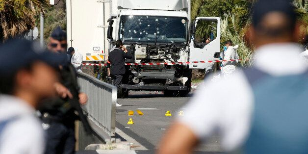 French police secure the area as the investigation continues at the scene near the heavy truck that ran...