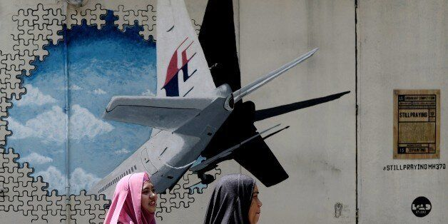 Malaysian women walk in front of a mural of missing Malaysia Airlines MH370 plane in a back-alley in...