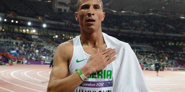 Algeria's Taoufik Makhloufi celebrates after winning the men's 1500m final at the athletics event during...