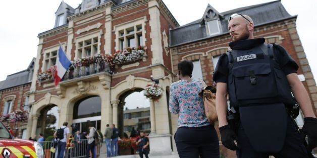 A French police officer stands guard by Saint-Etienne-du-Rouvray's city hall following a hostage-taking...