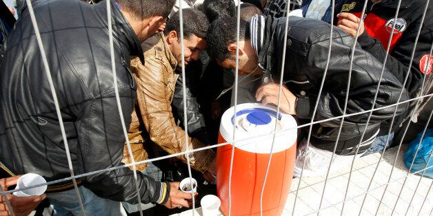 People fleeing the unrest in Tunisia drink water after they arrive at the southern Italian island of...