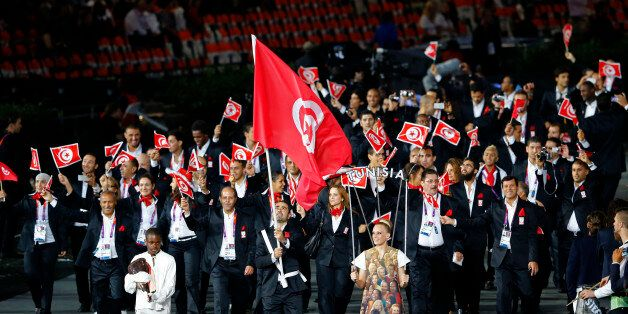 Tunisia's flag bearer Heykel Megannem holds the national flag as he leads the contingent in the athletes...