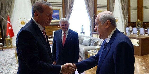 Turkey's President Recep Tayyip Erdoganl left, greets Devlet Bahceli before a meeting in Ankara, Turkey,...