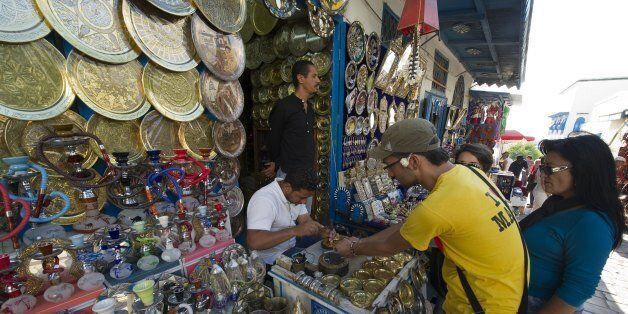 Tourists look at the stall of a street vendor in Sidi Bou Said on October 19, 2011, days before a historic...