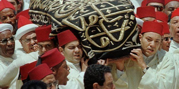 King Mohamed VI, right, and his brother Moulay Rachid, left, carry the coffin containing the remains...