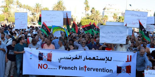 Libyan protesters hold banners and placards during a demonstration to protest against the French military...