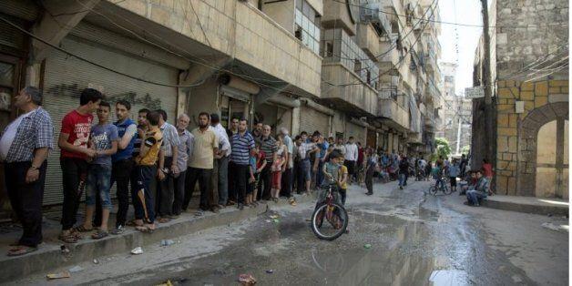 Des Syriens font la queue pour acheter du pain à Alep le 12 juillet