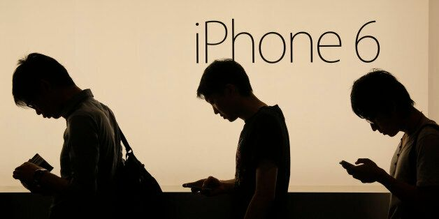 FILE - In this Friday, Sept. 19, 2014, file photo, people wait to buy the new Apple iPhone 6 and 6 Plus...