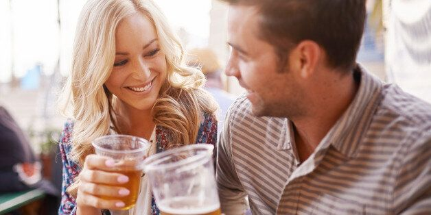 romantic couple drinking beer in plastic cups at outdoor bar with lens
