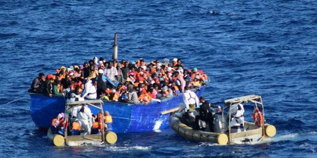 Migrants sit in their boat during a rescue operation by Italian navy ship Borsini (unseen) off the coast...