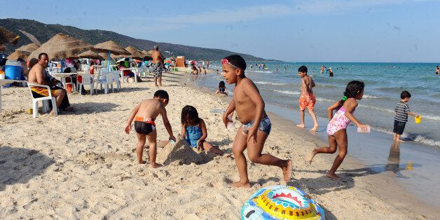 Children play on the beach in the Ghar El Melh suburb of Bizerte on July 1, 2012 as temperatures reached...