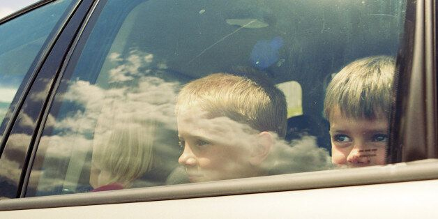 Two boys (4-9) in car, looking through