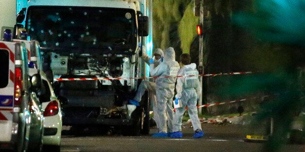 French police forensic officers stand next to a truck July 15, 2016 that ran into a crowd celebrating...