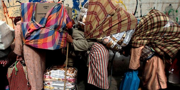 Women are bent double by sacks of goods at the Spain-Morocco border near Spain's North African enclave...