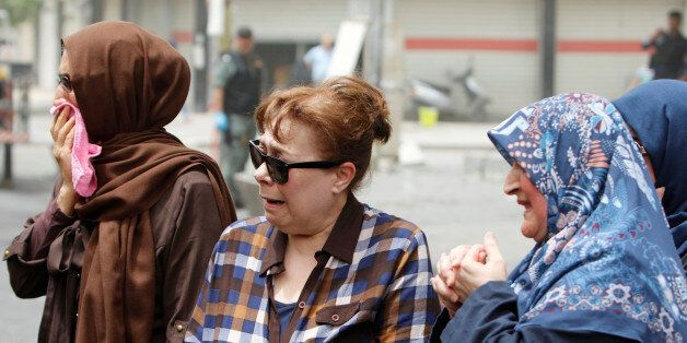 Women react at the site after a suicide car bomb attack at the shopping area of Karrada, a largely Shi'ite...