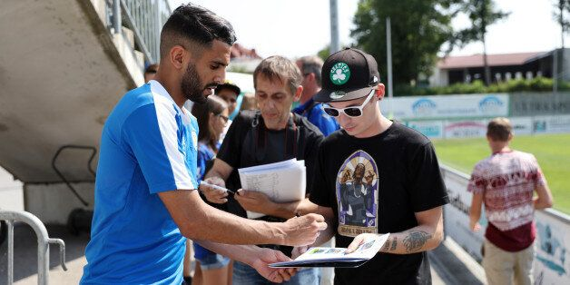 LEICESTER, ENGLAND - JULY 12: Leicester City's Riyad Mahrez signs autographs during the Leicester City...