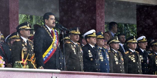 President Nicolas Maduro, second left, waits to speak during the Venezuela Independence Day parade in...