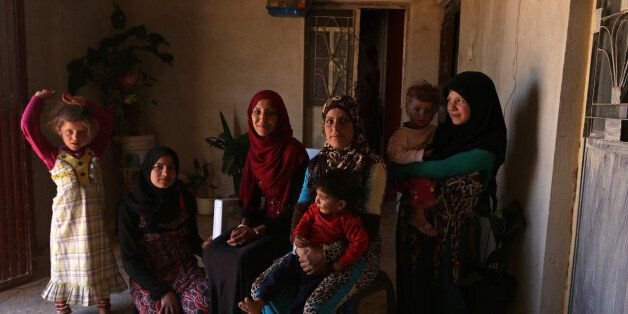 Souad Hamidi (3rd L), 19, poses for a photograph with other members of her family inside their home,...