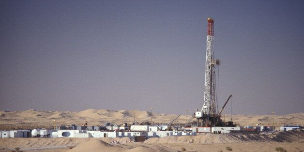 An Oil & Gas Industry drilling rig is surrounded by portable housing units and equipment in support of...