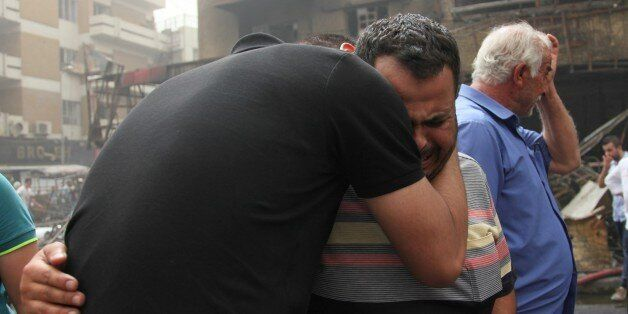 BAGHDAD, IRAQ - JULY 03: Iraqi people who lost their relatives mourn after a suicide car bombing, claimed...