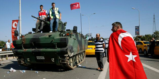A man wrapped in a Turkish flag walks past a military vehicle in front of Sabiha Airport, in Istanbul,...