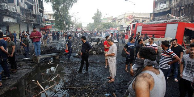 People gather at the site of a suicide car bomb in the Karrada shopping area, in Baghdad, Iraq July 3,...