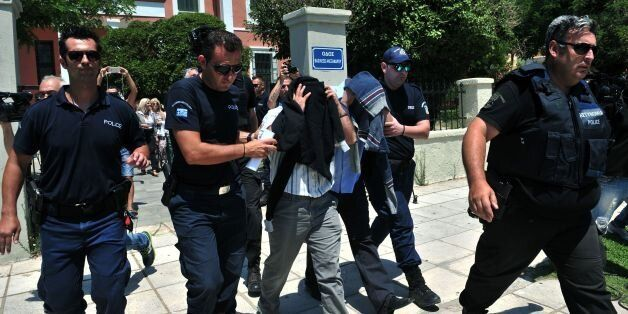 Turkish officers escorted by Greek police officers leave the courthouse of Alexandroupoli after appearing...