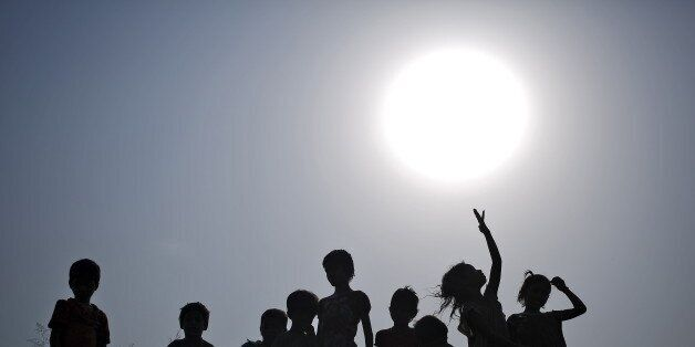 Children with their containers are silhouetted against the sun as they wait to fill drinking water from...