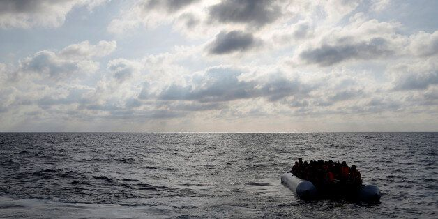 Migrants in a dinghy await rescue by the Migrant Offshore Aid Station (MOAS) around 20 nautical miles...