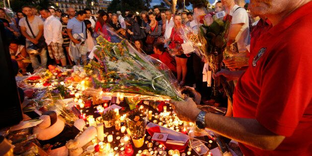People gather to leave flowers in tribute to victims the day after a truck ran into a crowd at high speed...