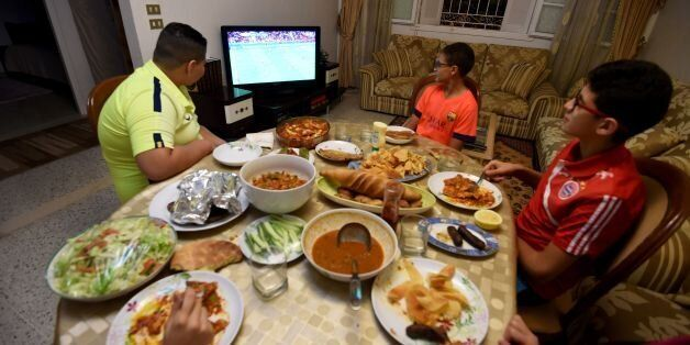 A Tunisian family watches a Euro 2016 football match during the break of Ramadan fast on June 17, 2016...