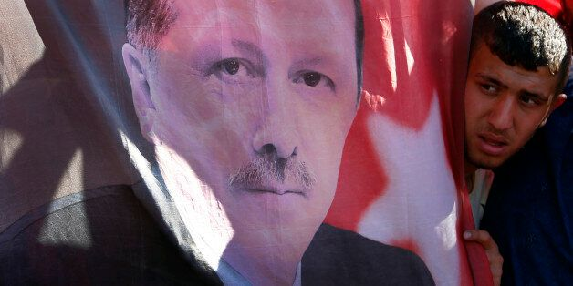 A Turkish man looks towards a portrait of Turkish President Recep Tayyip Erdogan during a protest against...