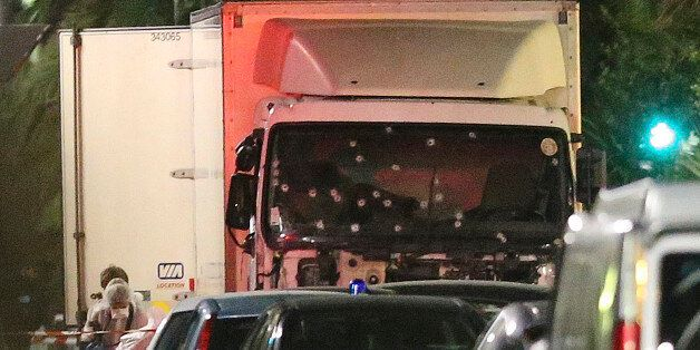 A policeman stands, watching the truck used for the attack near the scene of an attack after a truck...