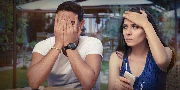 Young adult couple with smart phones upset out on a