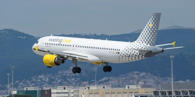 An airplane of the Spanish low-cost airline Vueling lands at Barcelona's airport in El Prat de Llobregat...