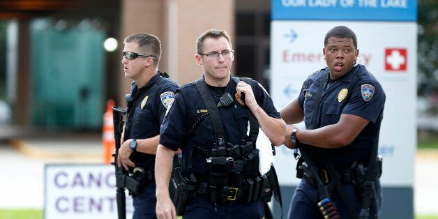 Police guard the emergency room entrance of Our Lady Of The Lake Medical Center, where wounded officers...
