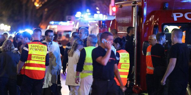 Police officers, firefighters and rescue workers are seen at the site of an attack on the Promenade des...