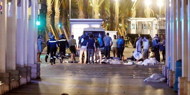 People stand next to covered bodies in the early hours of Friday, July 15, 2016, on the Promenade des...